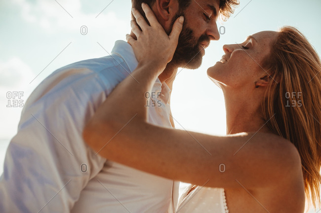 Close up of a romantic couple spending intimate moments outdoors. Woman holding man close to her to kiss.