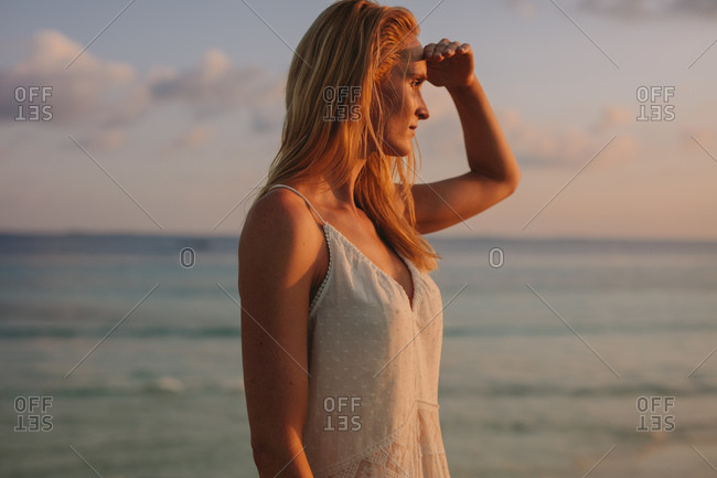 Portrait of a woman standing near the sea looking away. Tourist woman looking at the sea blocking the sun rays with her hand.