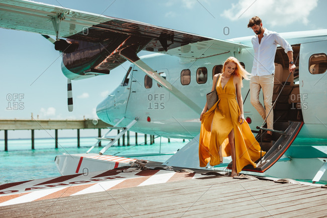Couple on a luxury holiday at an island resort. Couple walking out of a sea plane on reaching their holiday destination.