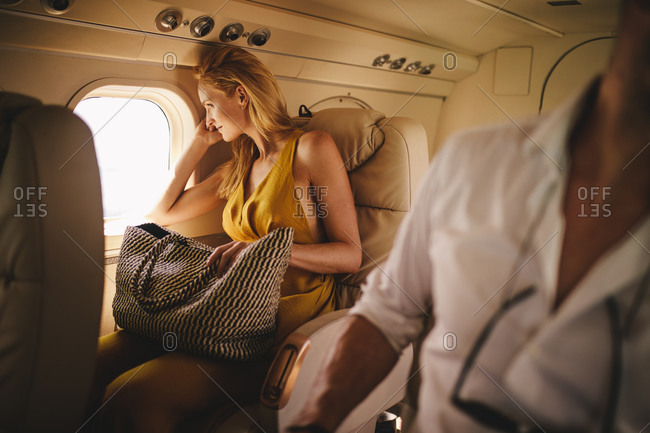 Woman sitting in an airplane looking out of the window. Woman on a holiday travelling in an aircraft.