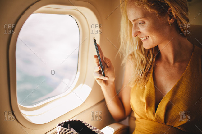 Close up of a woman sitting in an aircraft taking photos from the window. Woman travelling in luxury airplane sitting at the window.