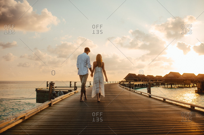 Rear view of a couple walking on a jetty at a luxury resort. Couple in love walking to their overwater villa at a resort holding hands.