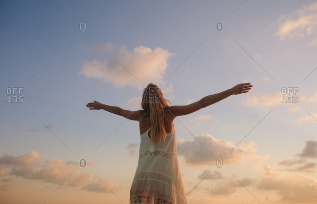 Rear view of a woman standing outdoors with arms stretched enjoying nature. Portrait of a relaxed and happy woman with open arms looking at the sky.
