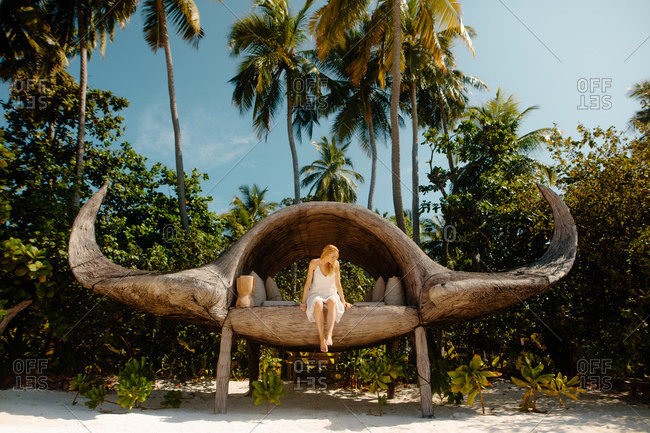 Tourist woman relaxing in a manta shaped lounge at a beach resort. Woman on a tropical holiday enjoying the warm sunshine.