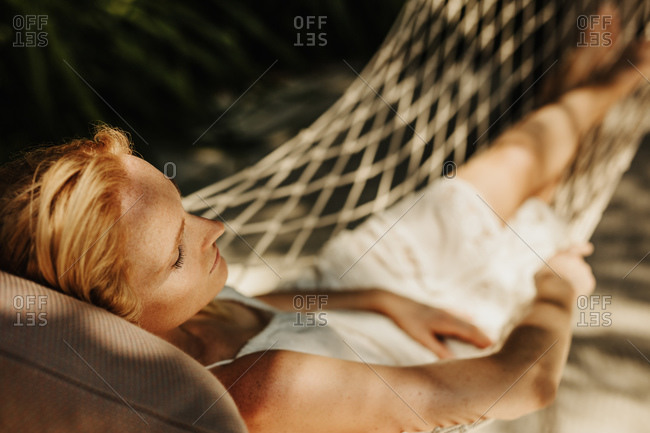 Woman relaxing in a hammock outdoors. Tourist woman sleeping in a rope swing on a sunny day.