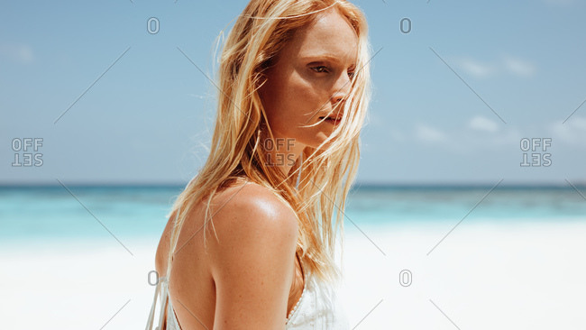 Close up of a caucasian woman standing on beach. Woman on beach vacation with hair flying on face in deep thought.