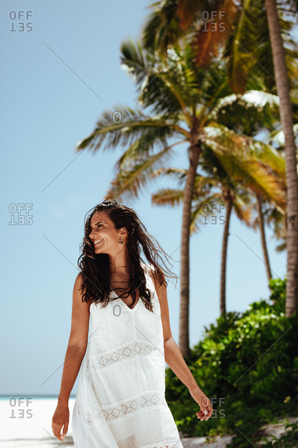 Portrait of a smiling woman on a beach. Cheerful woman on holiday walking on a tropical beach .