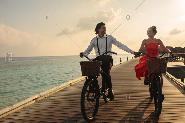 Close up of a couple on a holiday at a luxury resort riding bicycles. Formally dressed man riding bicycle with his girlfriend on a jetty.