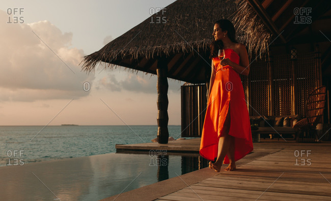 Woman on a holiday walking on an overwater villa at sunset. Tourist woman in red sundress walking on an overwater bungalow holding a wine glass.