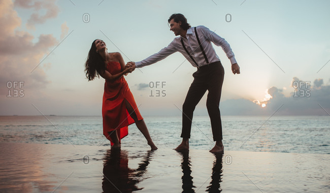 Romantic couple on a holiday having fun at an infinity pool holding hands. Couple in love enjoying a holiday at sunset.