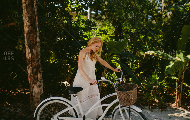 Woman standing in a tropical park holding a bicycle. Tourist woman enjoying a bicycle ride at a beach resort.