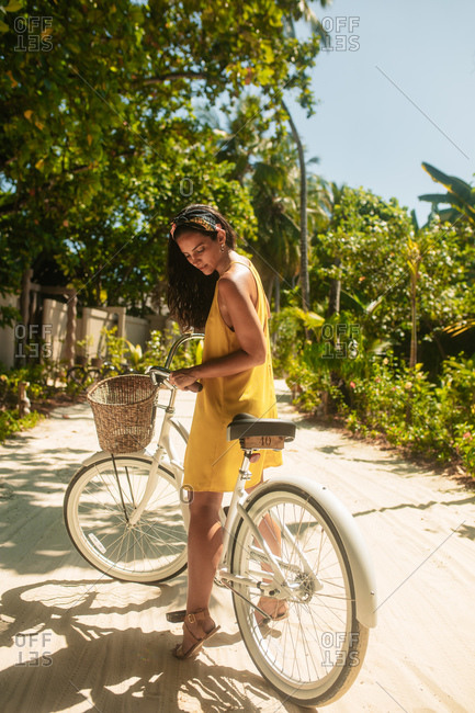 Portrait of a woman riding a bicycle. Woman on a holiday at a tropical resort enjoying a bicycle ride.