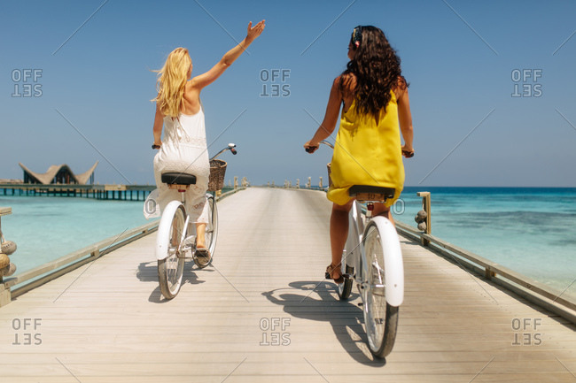 Tourist women having fun riding bicycles on a jetty. Rear view of friends enjoying a bicycle ride to an overwater villa.