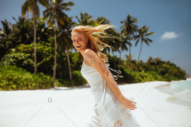 Side view of a tourist woman running on beach. Smiling woman being playful on her holiday at a tropical beach.
