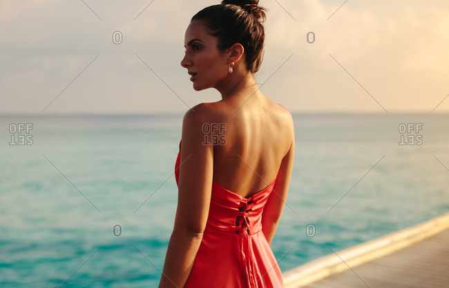 Rear view of a tourist woman standing near the sea. Woman enjoying the sea view standing on a jetty on a sunny day.