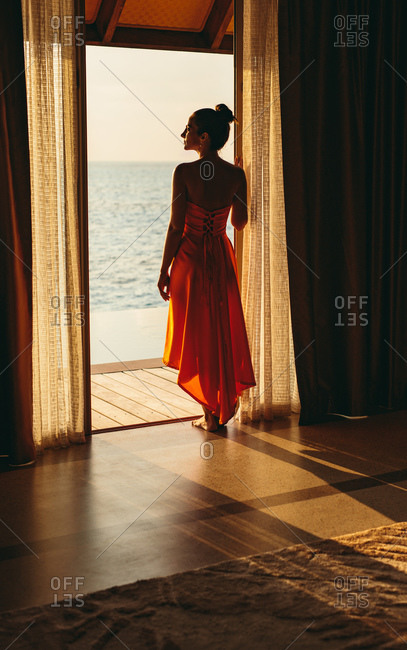 Rear view of a woman standing at the door of an overwater villa and looking at the sea. Tourist woman enjoying sea view from a luxury overwater villa.