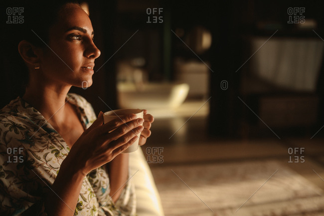Close up of a woman drinking coffee. Woman holding coffee cup with both hands and thinking.
