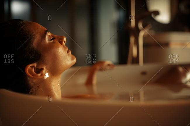 Close up of a woman bathing in a bathtub. Woman relaxing in a bathtub with closed eyes.
