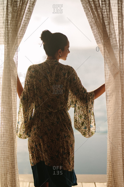 Portrait of a woman standing near the door of an overwater villa. Rear view of a tourist woman enjoying the beautiful sea view standing on an overwater bungalow.