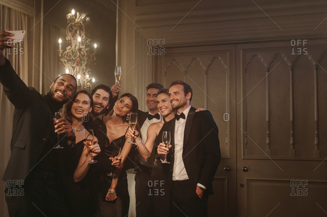 Man taking selfie with his friends at a celebrating event party. Group of multi-ethnic friends posing for a selfie together at gala night.