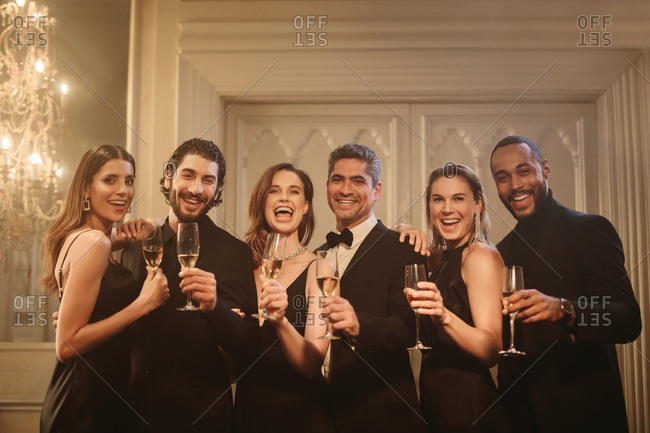 Group of friends celebrating new years eve together. Smiling multi-ethnic men and women standing together toasting champagne and looking at the camera.
