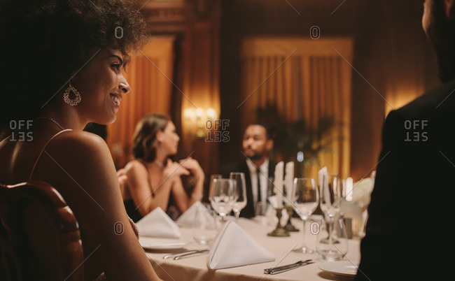 African woman at dinner party with friends. High society people having gala dinner party.