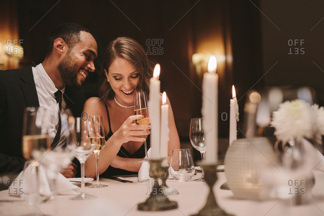 Young couple sitting at dining table with candles having wine. Loving man and woman at a gala dinner party.