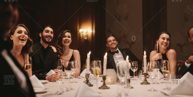 Group of friends sitting around a table at dinner party. High society people having gala dinner party.
