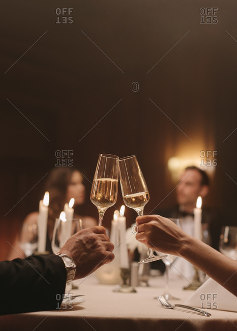 Cropped shot of a couple toasting champagne at dinner party. Loving man and woman at a gala dinner party celebrating with drinks.