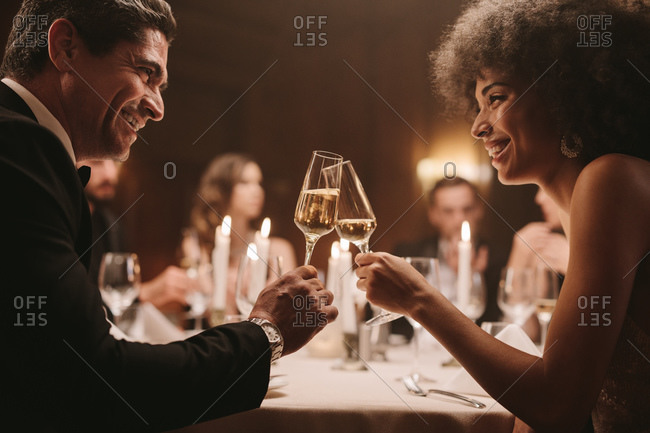 Couple at gala dinner night toasting champagne. Friends at party enjoying drinks.
