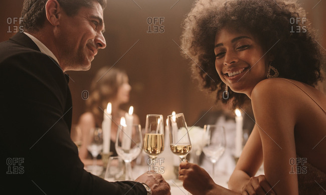 Beautiful couple at new years dinner party. Loving man and woman at a gala dinner party with drinks.