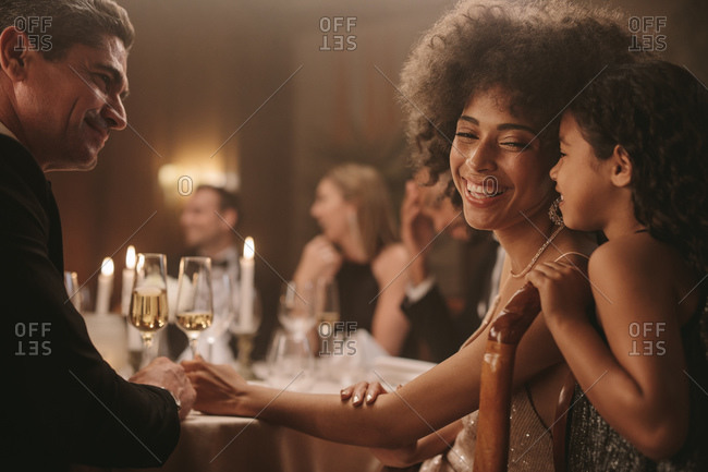 Cute girl talking with her mother and a man sitting at gala dinner party. Girl having fun with her mother sitting with friends at gala party.