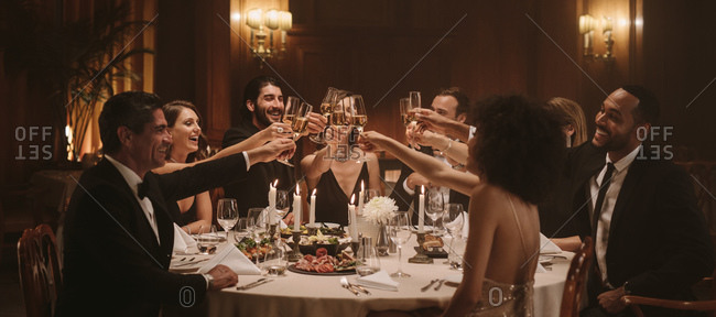 Group of people toasting drinks at a gala party. Multiracial friends enjoying new years party with drinks.