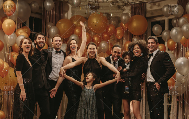 Multi-ethnic group of people standing together and having fun at new years party. Group of men and women with little girl looking at camera and smiling with confetti falling around.