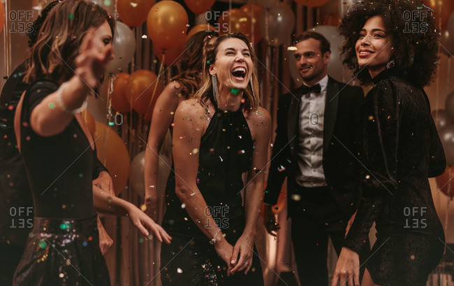 Attractive woman laughing while dancing with friends. Group of men and women dancing at new years eve party at night club.