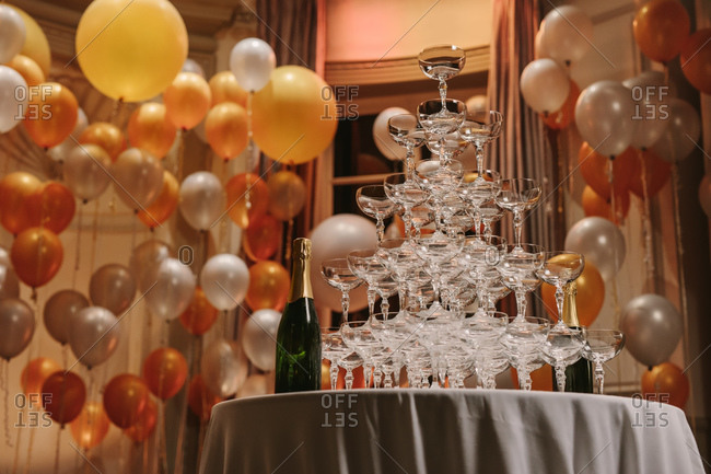 Champagne glasses arranged in tower shape for new year party. Pyramid of champagne glasses at a party.