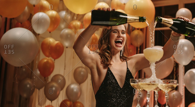 Excited young woman filling champagne into a tower glasses at gala night party. Beautiful female socialite enjoying at new years party.