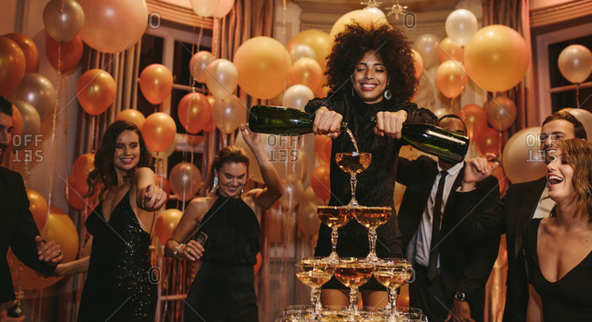 African female filling champagne pyramid with two bottles and friends dancing around at a party. Multi-ethnic group of people enjoying at a party.