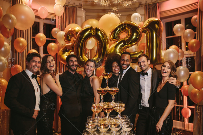 Pyramid of champagne glasses with people standing together at a gala party. Portrait of party people with tower of champagne glasses at new years eve.