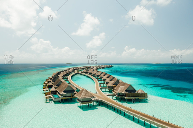Aerial view of overwater villas in a symmetrical design at a luxury island resort. Luxury tourist resort at an island in the Maldives.