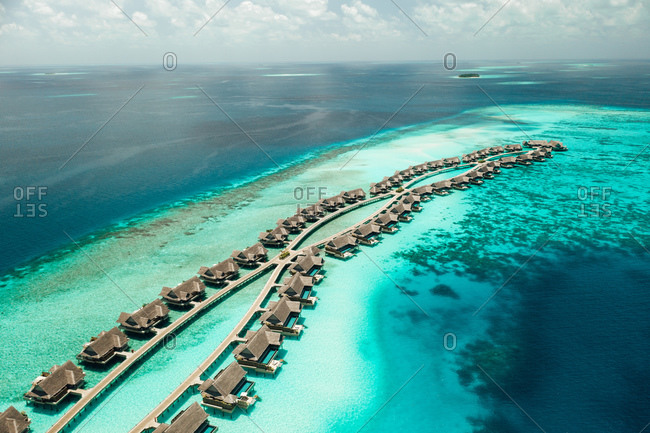 Aerial view of a tourist resort at an island in the Maldives. Series of overwater villas at a luxury island resort.