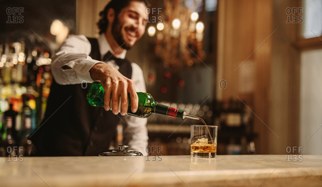 Barman pouring whiskey in a glass over bar counter. Bartender preparing a drink for guest at a pub.