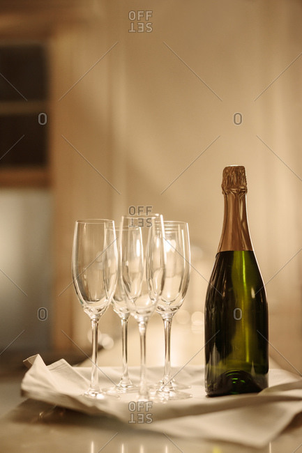 Bottle of champagne with empty glasses on bar counter. Champagne flutes with bottle of champagne at party.
