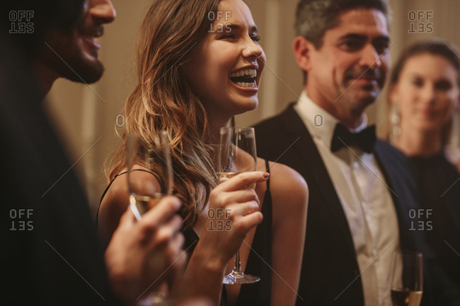 Group of friends having a fun at party. High society people talking and having a good time together at a gala night.