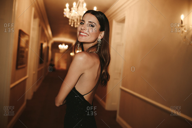 Gorgeous woman standing in a corridor looking back at the camera. Young caucasian female in evening gown.
