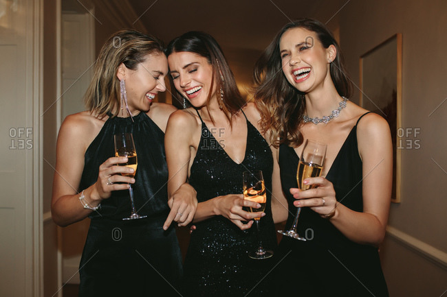 Group of women with champagne glasses walking in corridor. Best friends enjoying at a gala night party.