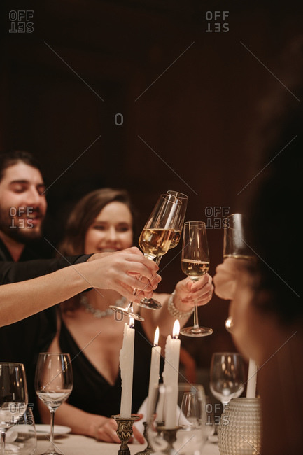 Group of men and women celebrating party with champagne. High society people at a dinner party toasting drinks.