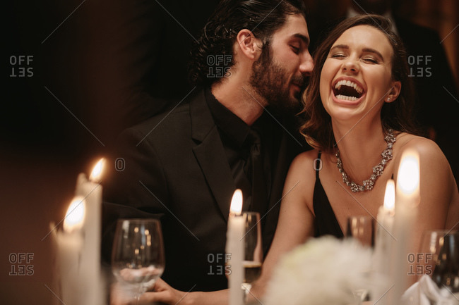 Man whispering in to woman's ear at a dinner party. Loving couple having a fun at a gala dinner event.