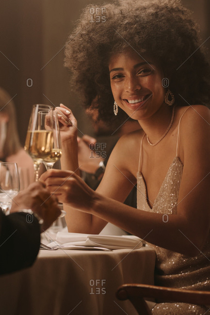 Attractive african woman at a dinner party toasting champagne with a friend. Smiling woman enjoying at a gala dinner event.