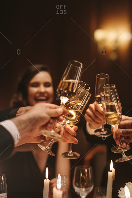 Group of men and women enjoying a dinner party, toasting champagne glasses. Group of friends having drinks at gala night.